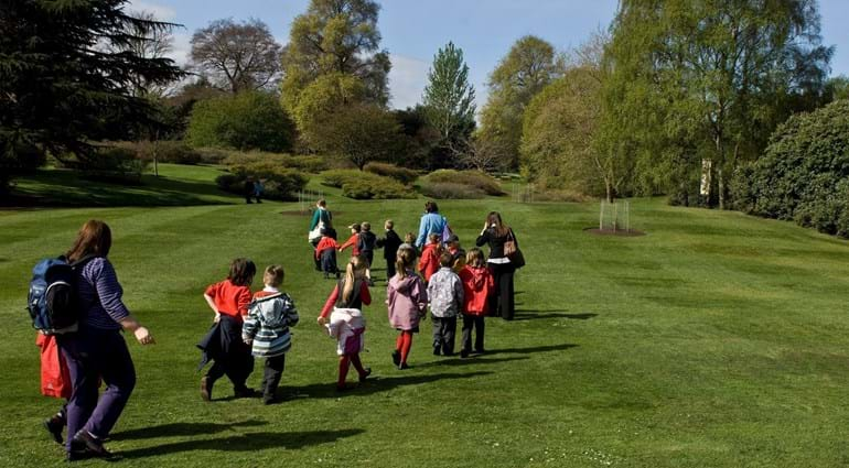 A school class waling across a lawn in the Garden